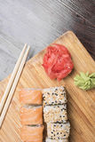 Rollos de sushi con las semillas de los salmones y de sésamo, el jengibre y el wasabi, palillos del sushi Fotografía de archivo libre de regalías