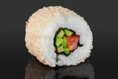 Rollos de sushi con las semillas del aguacate, de los salmones y de sésamo Fotos de archivo libres de regalías