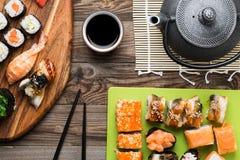 Rollos de sushi con los diversos pescados y aguacate, sistema de delicadezas Fotos de archivo