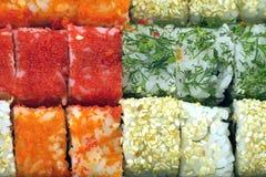 Rollos de sushi con los ingredientes como primer del fondo Foto de archivo