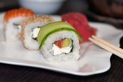 Rollos de sushi con los pescados, el pepino y el queso rojos de Philadelphia Foto de archivo