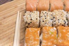 Rollos de sushi con los salmones, el sésamo blanco y negro, el caviar rojo y los palillos del sushi Fotos de archivo