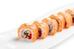 Rollos de sushi con los salmones, la anguila, el pepino y el tobiko en la placa blanca Imagen de archivo
