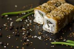 Rollos de sushi de la anguila con las semillas de la cebolla verde, del aguacate y de sésamo en fondo negro Fotografía de archivo libre de regalías