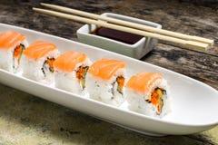 Rollos de sushi de los mariscos en el plato blanco con el sause de la soja Foto de archivo