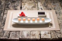 Rollos de sushi de los mariscos en el plato largo blanco con la salsa de soja Front View Fotografía de archivo libre de regalías