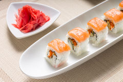 Rollos de sushi de los mariscos en la placa blanca con los palillos y las especias japonesas Fotografía de archivo