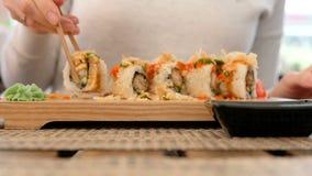Rollos de sushi del eatinf de la mujer en restaurante japon?s, cierre para arriba almacen de video