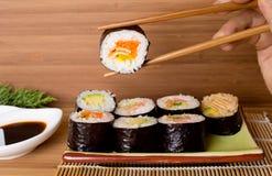 Rollos de sushi en fondo de madera Imagen de archivo