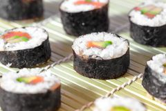 Rollos de sushi en la estera de bambú Jeringuilla del concepto design Cocina japonesa Imágenes de archivo libres de regalías