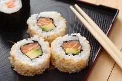 Rollos de sushi en la placa negra y los palillos Fotos de archivo