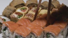 Rollos de sushi en un rollo de sushi del primer de la placa con los palillos de color salmón de la toma almacen de video