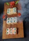 Rollos de sushi en un tablero de madera Imagen de archivo libre de regalías