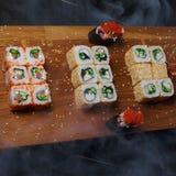 Rollos de sushi en un tablero de madera Fotografía de archivo