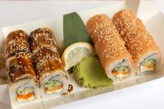 Rollos de sushi en una fiambrera blanca del papel del eco para llevar fotos de archivo