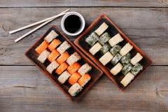 Rollos de sushi, palillos y cuencos japoneses de la salsa fotografía de archivo