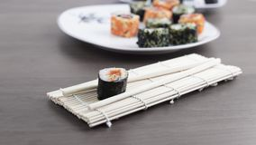 Rollos de sushi y palillos en una tabla de madera Fotos de archivo libres de regalías