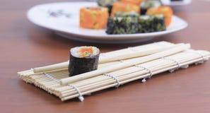Rollos de sushi y palillos en una tabla de madera Imagen de archivo libre de regalías