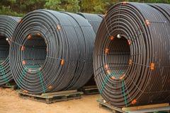 Rollos grandes de tubos en emplazamiento de la obra en bosque Imagen de archivo libre de regalías