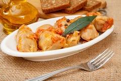 Rollos hechos en casa deliciosos de la col rellenos con arroz y carne en plato con la bifurcaci?n y botella de aceite de girasol foto de archivo libre de regalías
