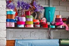 Rollos multicolores con las cintas en los estantes imagenes de archivo