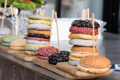 Rollos multicolores con las semillas de sésamo para cocinar las hamburguesas Imagen de archivo