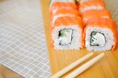 Rollos poner crema con la mentira de color salmón en un tablón de madera foto de archivo libre de regalías