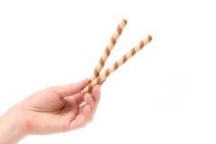 Rollos rayados asimientos de la oblea del chocolate de la mano fotos de archivo libres de regalías