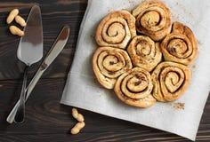 Rollos y nueces de canela en una mesa de desayuno de madera Fotografía de archivo libre de regalías