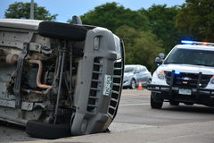 Totalled SUV in Rollover Wreck. An SUV rolled onto its side with a police cruiser in the background Royalty Free Stock Image