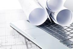 Rolls архитектурноакустических планов жилищного строительства светокопии на клавиатуре ноутбука стоковая фотография