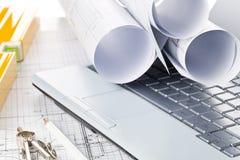 Rolls архитектурноакустических планов жилищного строительства светокопии на клавиатуре ноутбука с карандашем, компасами и уровнем стоковое фото rf