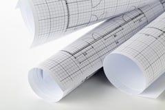 Rolls архитектурноакустических планов жилищного строительства светокопии на белой таблице стоковое фото rf