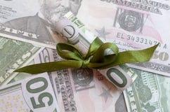 Rolls денег в ленте подарка на счетах долларов и евро Стоковая Фотография