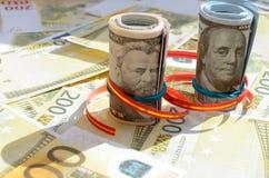 Rolls денег в ленте подарка на счетах долларов и евро Стоковое фото RF