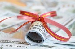 Rolls денег в ленте подарка на счетах долларов и евро Стоковые Изображения RF