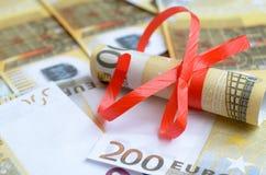 Rolls денег в ленте подарка на счетах долларов и евро Стоковые Изображения