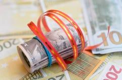 Rolls денег в ленте подарка на счетах долларов и евро Стоковые Фотографии RF