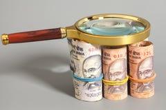 Rolls индийских примечаний рупии валюты с лупой Стоковое фото RF