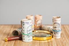 Rolls индийских примечаний рупии валюты с лупой Стоковые Фото