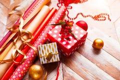 Rolls упаковочной бумаги рождества с лентами, подарками и bolls Стоковая Фотография RF
