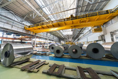 Rolls of aluminum and crane in production shop of plant. In special places Royalty Free Stock Image