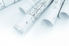 Rolls of architectural blueprints and floor plans on white. Background stock photography