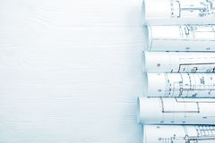 Rolls of architectural blueprints on white wooden desk. Rolls of architectural blueprints and technical drawings on white wooden desk royalty free stock images
