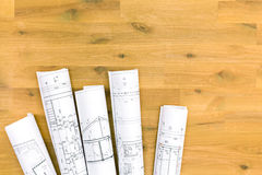 Rolls of architectural blueprints on wooden table Royalty Free Stock Images