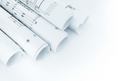 Rolls of architectural house floor plans on white background. Rolls of architectural house floor plans and blueprints on white background royalty free stock image