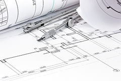 Rolls of architecture blueprint with drawing compass closeup Royalty Free Stock Images