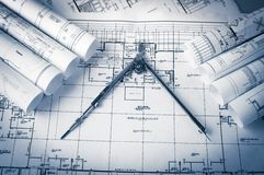 Rolls of architecture blueprints and house plans. On the table and drawing compass royalty free stock photos