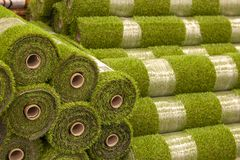 Rolls artificial grass in store of building materials. royalty free stock photography