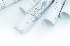 Rolls av arkitektoniska ritningar och golvplan på vit Arkivbild